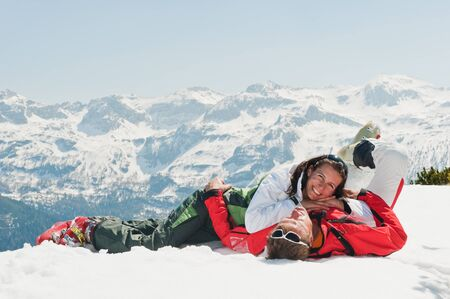 mid adult: Austria,Salzburg Country,Mid adult couple lying on snow in winter Stock Photo