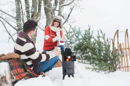 Austria,Salzburg Country,Flachau,Young man and woman drinking tea and sitting besides stove in winter