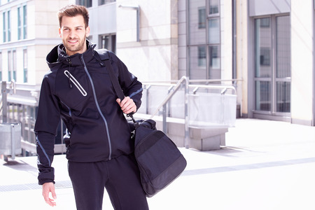 going: Young man wearing sports wear and bag, Madgeburg, Germany Stock Photo
