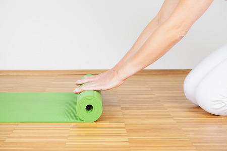 Woman practicing Yoga, woman rolling out yoga mat Stock Photo