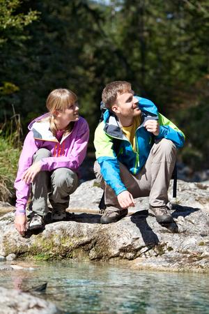 crouching: Germany,Upper Bavaria,Couple crouching near stream while hiking,smiling Stock Photo