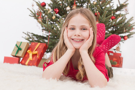 Girl lying on carpet, Christmas tree and gift in background, smiling, portrait