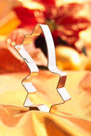 cookie cutter: Cookie cutter, shooting star shaped, on golden cloth Stock Photo