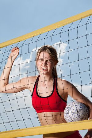 clenching teeth: Germany,Bavaria,Mauern,Young woman with beach volleyball clenching teeth