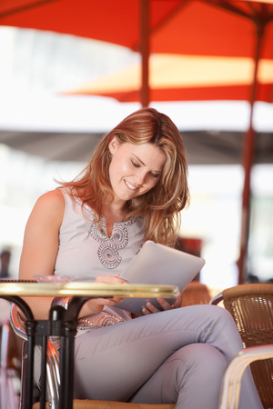 landshut: Germany,Lower-Bavaria,Landshut,Young woman sitting at street cafe with digital tablet,smiling