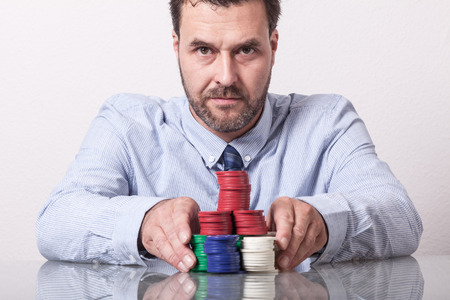 by placing: Mature man with poker chips on glass table, placing his bet Stock Photo