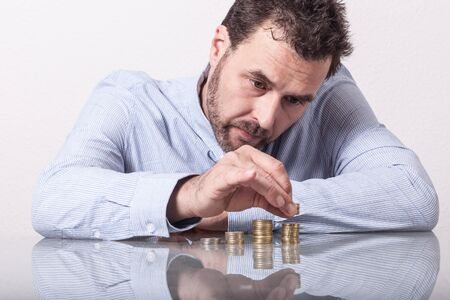 advising: Business man counting money, stacks of coins on office desk Stock Photo