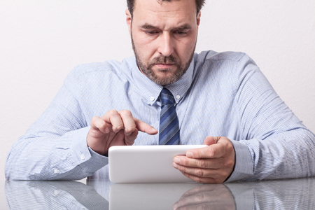 Business man on office desk, typing on tablet computer. Mature CaucasianEuropean adult, glass table with reflection.