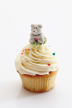 hundreds and thousands: Close up of vanilla buttercream cupcake with panda figurine against white background