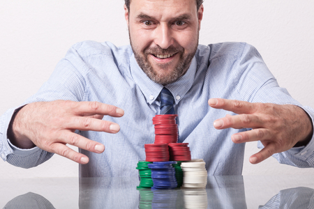 greedy: Mature man with poker chips on glass table, looking greedy Stock Photo