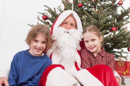girl sitting: Boy and girl sitting with santa claus smiling, portrait Stock Photo