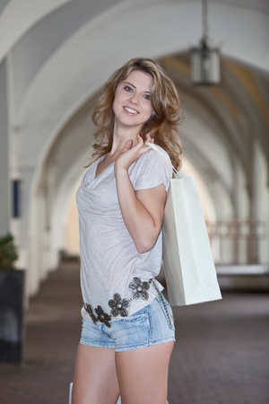 landshut: Germany,Lower Bavaria,Landshut,View of young woman wlking with shopping bags in city,smiling,portrait