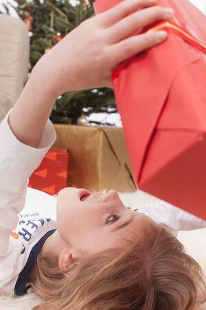 holding aloft: Boy lying on back and holding Christmas gift, smiling