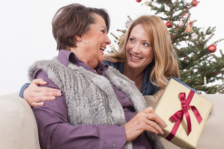 woman on couch: Senior woman and adult woman smiling with Christmas gift Stock Photo