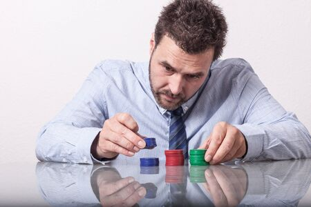 poker: Mature man with poker chips on glass table, sorting stacks Stock Photo