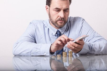 figuring: Mature man at desk with stacked euro coins using smart phone