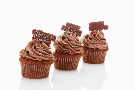 hundreds and thousands: Close up of buttercream chocolate cupcake with chocolate sticker against white background