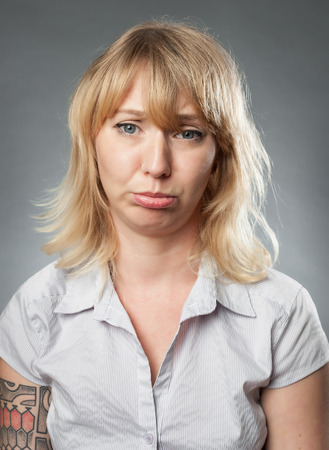 pouting: Young woman portrait on grey background, pouting expression
