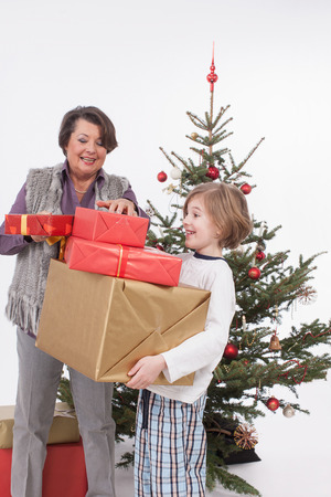 generation gap: Boy holding Christmas gifts while senior woman adjusting, smiling