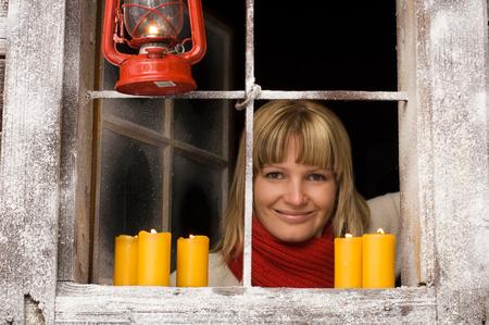 anticipate: Austria, Salzburger Land, Young woman looking through window, candles burning on windowsill