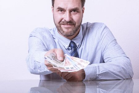 fanned: Mature man offering fanned euro notes Stock Photo