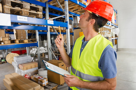 Germany,Bavaria,Munich,Manual worker with clipboard in warehouse