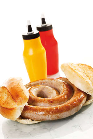 indulgence: German Bratwurst, fried sausage and bread roll, close-up