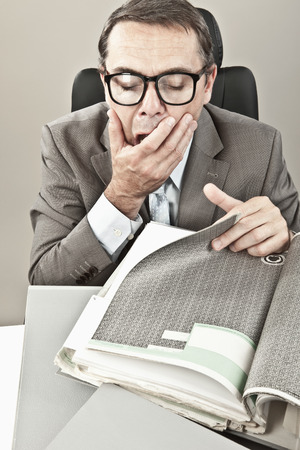 overstress: Close up of mature businessman yawning in office Stock Photo