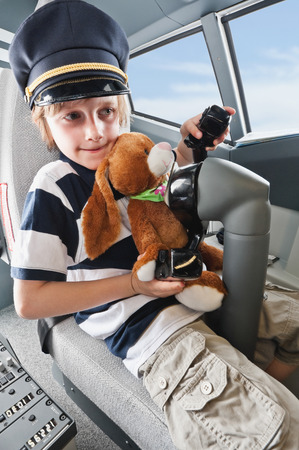soft toy: Germany,Bavaria,Munich,boy wearing captains hat and holding soft toy in airplane cockpit