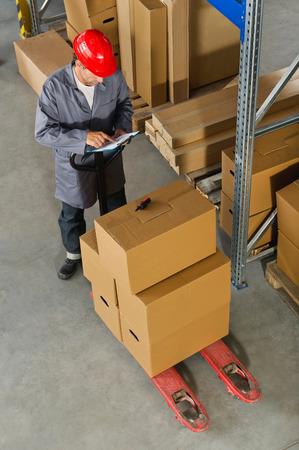 warehouseman: Germany,Bavaria,Munich,Manual worker checking list in warehouse