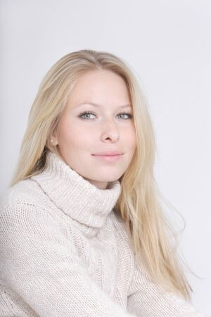 turtleneck: Young woman wearing turtleneck jumper against white background,smiling,close up Stock Photo