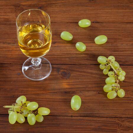 şarap kadehi: Wine glass and green grapes on wood Stok Fotoğraf