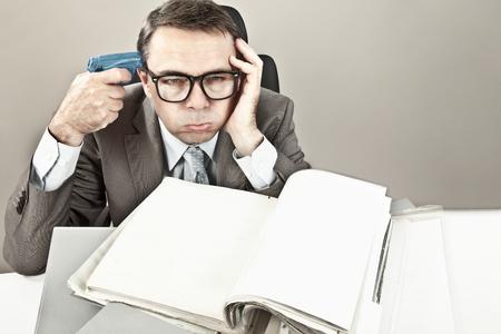 overstress: Close up of mature businessman at office holding gun