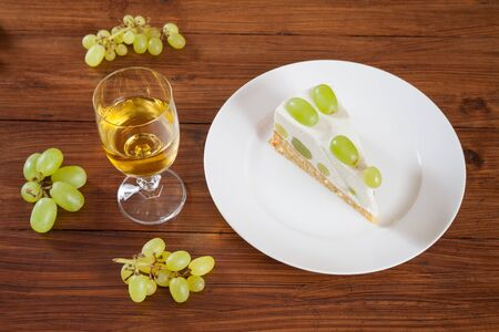 torte: Piece of grape torte with green grapes on plate, white wine glass