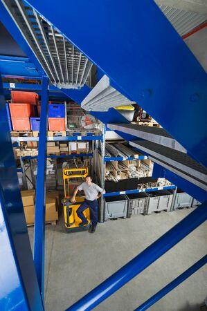 warehouseman: Germany,Bavaria,Munich,Manual worker standing by pallet in warehouse