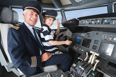 pilot cockpit: Germany,Bavaria,Munich,Senior pilot and boy in airplane cockpit Stock Photo