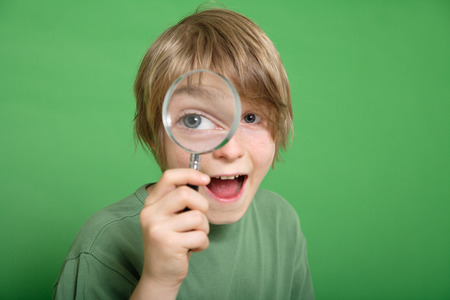 scrutiny: Close up of boy looking through magnifying glass against green background
