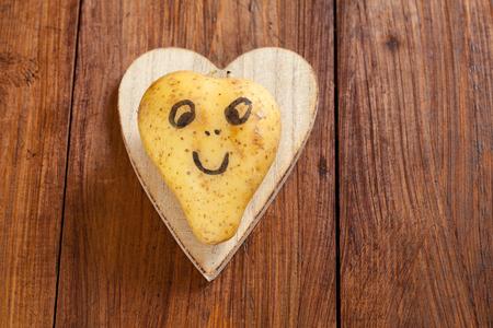 cara de alegria: Patata en forma de coraz�n con la cara feliz en la madera, espacio de copia Foto de archivo