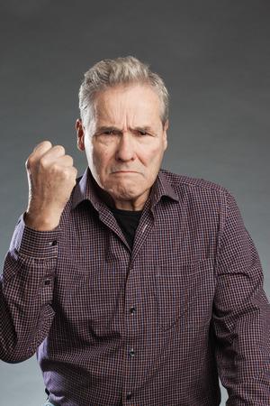 to tend: Älterer Mann ballt wütend die Faust Stock Photo