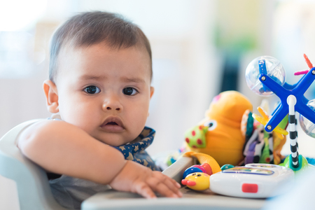 Close up of hispanic infant boy in baby chair with toys