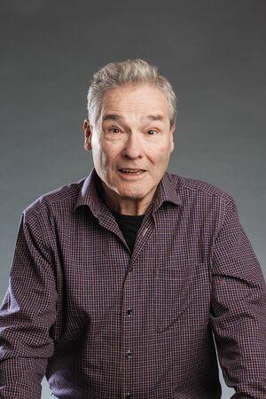Älterer Mann lächelt freudig überrscht
