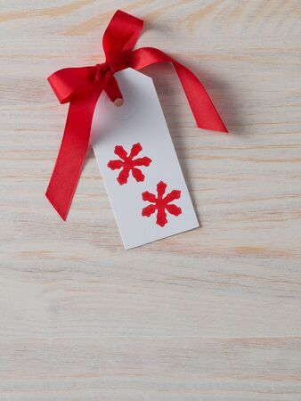 christmastime: Christmas, gift tag, printed, red ribbon, background wood Stock Photo