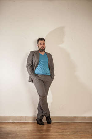 relaxed business man: Relaxed business man with beard leaning on wall Stock Photo