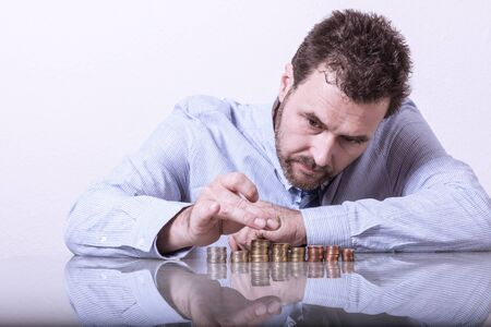 counting money: Business man counting money, stacks of coins on office desk Stock Photo