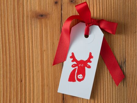 Christmas, gift tag, printed, red ribbon, background wood Stock Photo