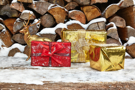 capreolus: Christmas presents and deer figurine in front of woodpile