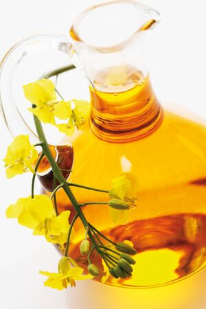 oil rape: Rapeseed oil in jar with rape blossom on white background Stock Photo