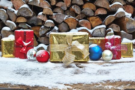 woodpile: Christmas presents and baubles in front of woodpile