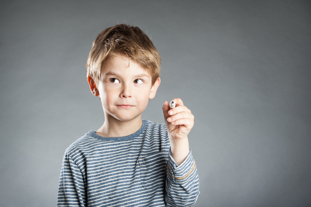 resourceful: Portrait of boy with pen, thoughtful, grey background