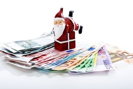 christmas bonus: Santa Claus on gift lying on fanned euro notes